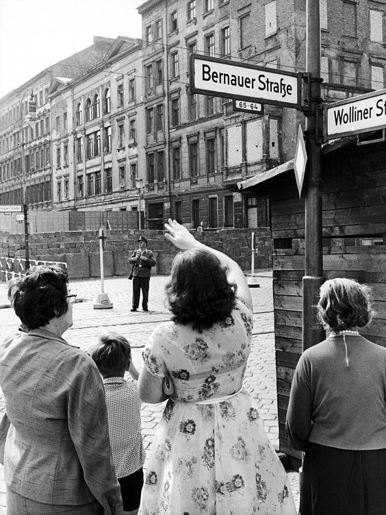 FILE - The Aug. 13, 1962 file photo shows West Berliners waving to relatives in East Berlin one year after the Berlin Wall was erected at Bernauer Strasse in Berlin. (AP Photo/Werner Kreusch, file)