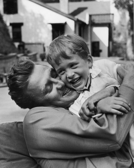 Actor Kirk Douglas hugging son Michael, who is laughing.